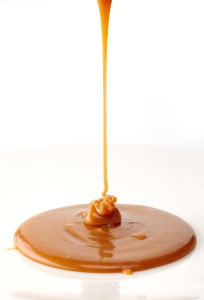 pouring sweet caramel sauce on a white background